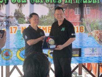 Datuk Pang Yuk Ming receiving a memento from Datuk Admund Looh (CEO of Borneo Divers)