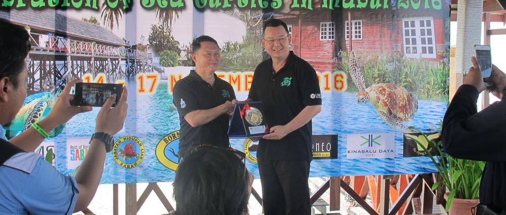Datuk Pang Yuk Ming receiving a memento from Datuk Admund Looh (CEO of Borneo Divers)